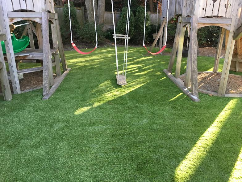 Synthetic grass under a kids playset