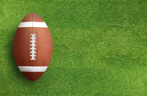 American,Football,Ball,On,Green,Grass,Field,Background.